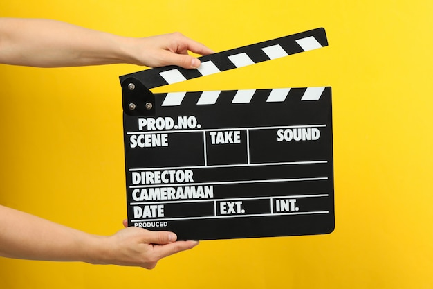 Female hands holding clapper board on yellow