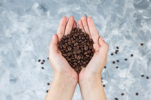 コーヒー豆を平らに保持している女性の手は、汚れた灰色の背景に横たわっていた
