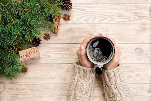 Female hands holding coffee cupon wooden table with chrisstmas decoration. top view