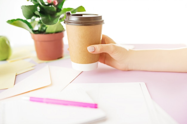 Female hands holding coffee on trendy pink desk.