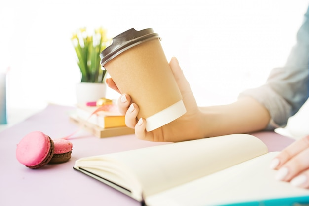 Female hands holding coffee. trendy pink desk.