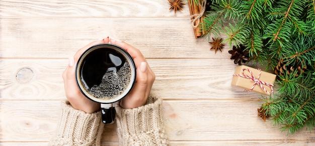 Женские руки держат кофе с рождественским украшением Premium Фотографии