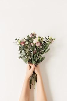 白い壁にカラフルなバラの花の花束を保持している女性の手。
