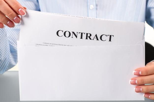 계약서를 들고 있는 여성의 손. 계약서가 있는 여자. 봉투를 열고 읽습니다. 고용주의 결정.
