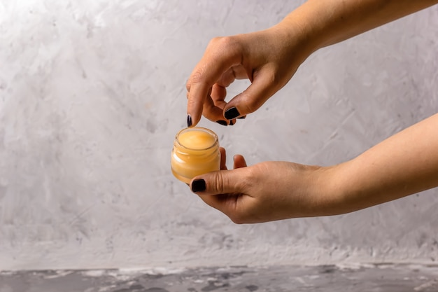 Female hands holding cosmetic product in a glass jar