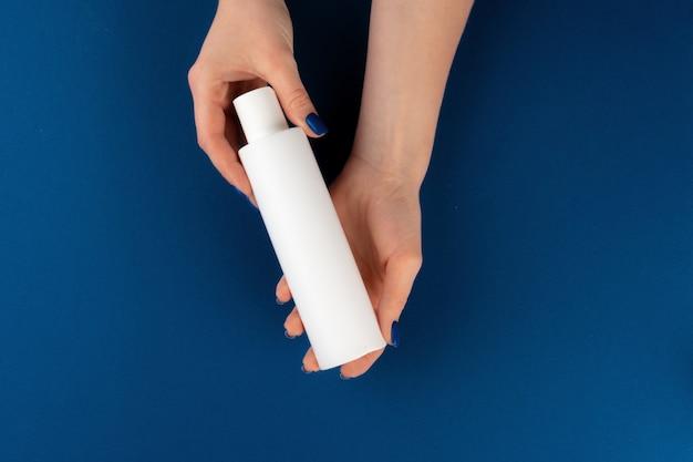 化粧品容器を手で押し女性の手