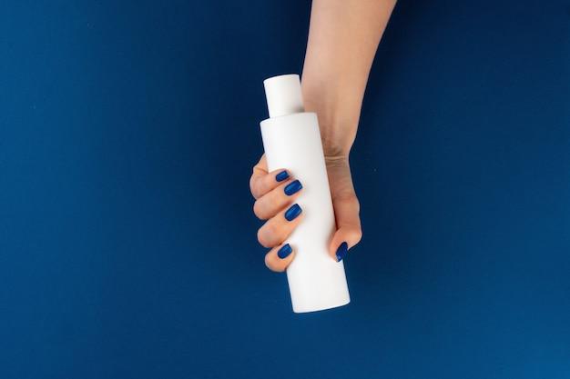 青い背景の手で化粧品コンテナーを保持している女性の手。上面図