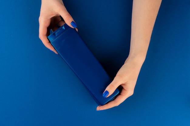 青い背景の手で化粧品コンテナーを保持している女性の手