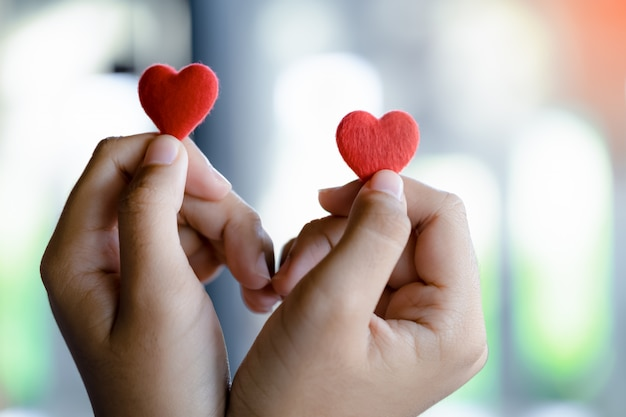 Female hands holding a couple red heart, selective focus