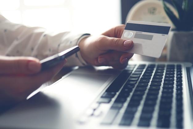 ノートパソコンの近くでクレジットカードと電話を保持している女性の手。閉じる。オンライン支払い。銀行振込。
