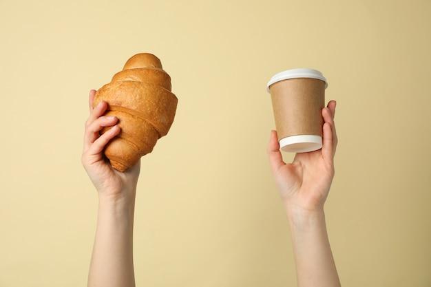 Женские руки, держа круассан и чашку кофе на бежевом фоне, крупным планом