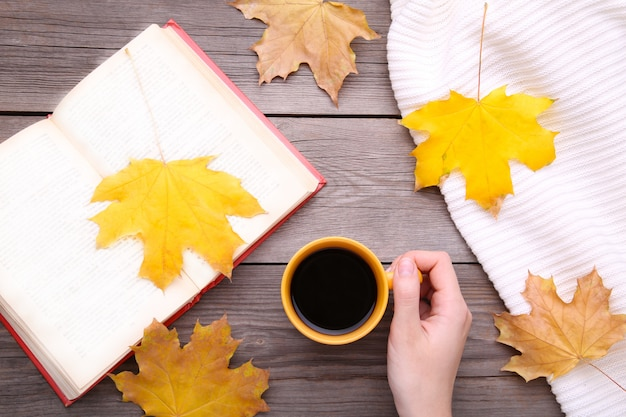 Female hands holding cup of black coffee with autumn leaves and book on grey