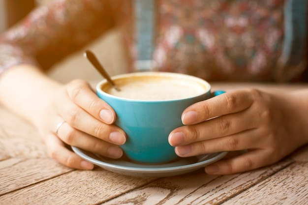 Female hands holding cup of coffee with foam on table