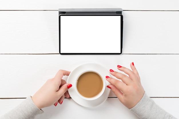 デジタルタブレットコンピューターで木製のテーブルにコーヒーのカップを保持している女性の手。