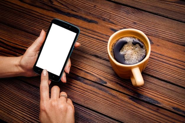 木製のテーブルにコーヒーのカップを保持している女性の手