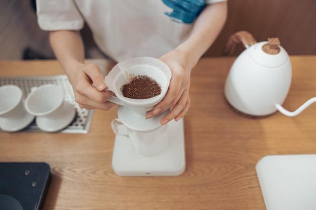 종이 필터가 달린 커피 한 잔을 들고 있는 여성의 손