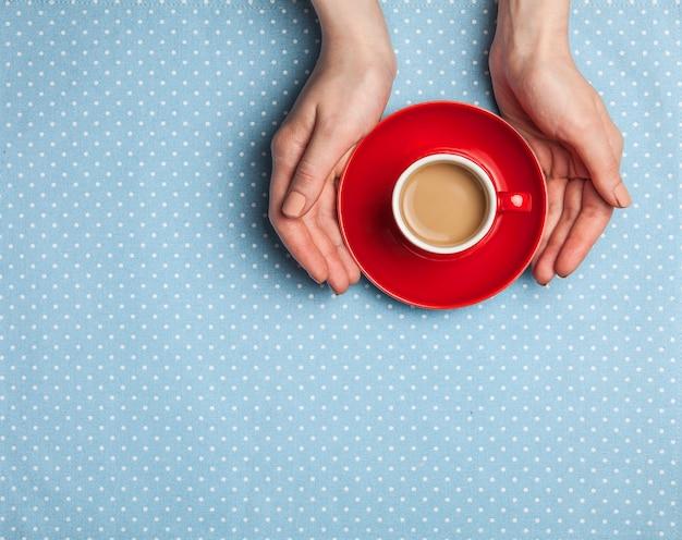 一杯のコーヒーを保持している女性の手