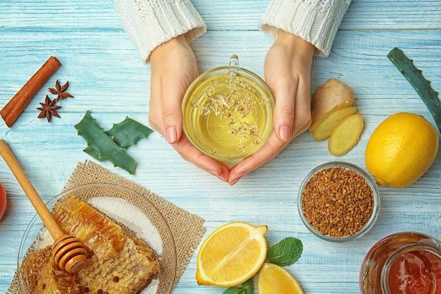 Женские руки, держа чашку травяного чая на деревянных фоне