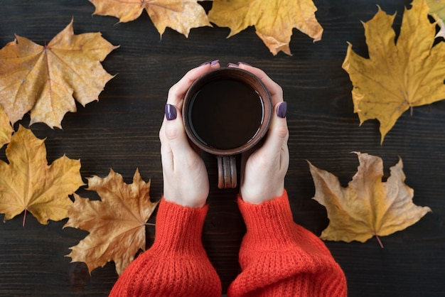 Female hands holding cup of tea on wooden surface with fallen autumn leaves.