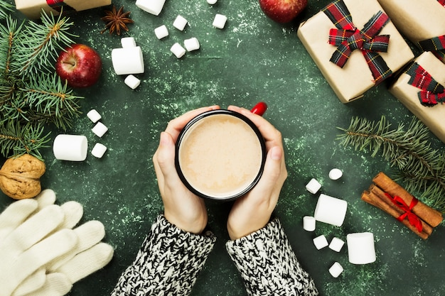 Female hands holding cup with hot chocolate and various attributes of holiday on a green surface. top view