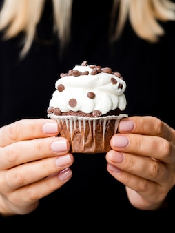 Female hands holding delicious muffin