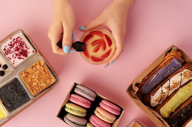 Женские руки, держа в руках десерт среди свежих кондитерских изделий, крупным планом