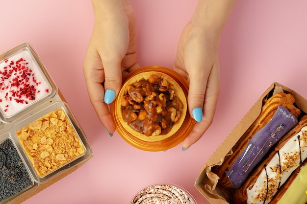 Женские руки, держа в руках десерт среди свежих кондитерских изделий