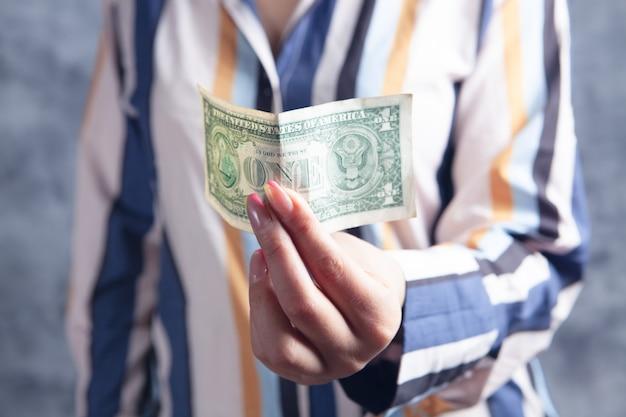 Female hands holding a dollar bill