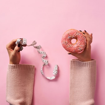 Female hands holding donut and measuring tape over pink background