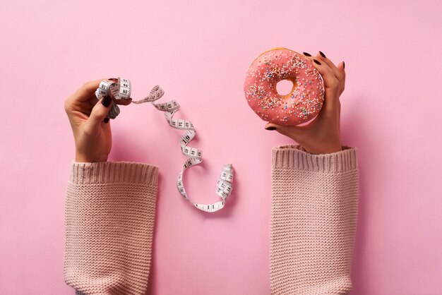 Female hands holding donut and measuring tape over pink background.