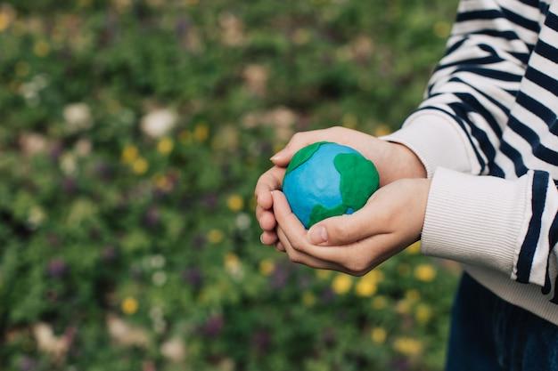 緑の春の背景に地球を保持している女性の手。