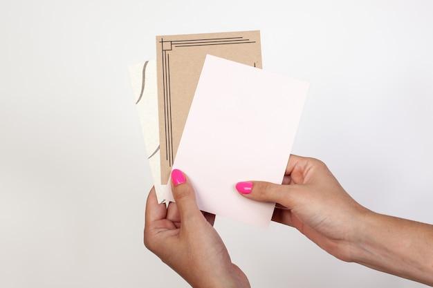 テキスト用の空の名刺を持っている女性の手または白いグリーティングカードはがきのモックアップをデザイン...