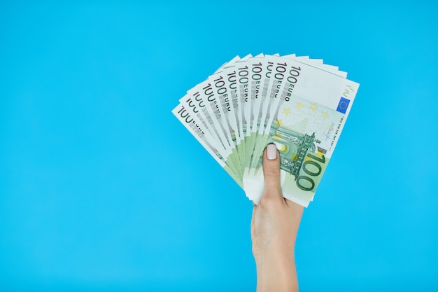 Female hands holding euro banknotes on blue.