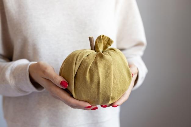 Женские руки, держа ткань тыквы день благодарения и концепция хэллоуина подарки фуросики