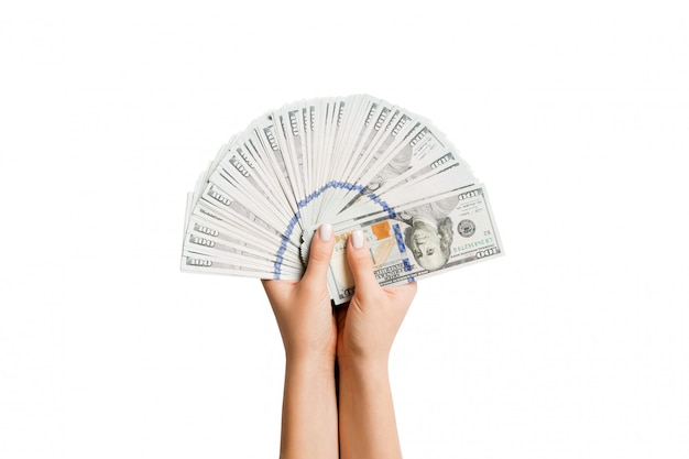 Female hands holding a fan of dollar banknotes on isolated background. success and investment concept