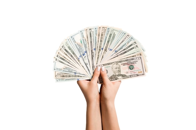 Female hands holding a fan of dollar banknotes on isolated surface