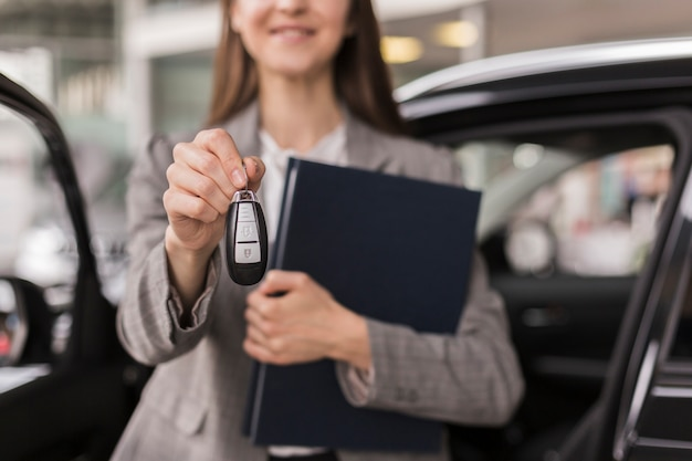 Mani femminili che tengono una cartella e le chiavi dell'automobile