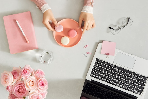 Female hands holding french macarons on trendy color white desk. woman and stylish workplace.