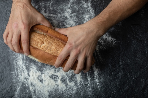 Female hands holding freshly baked bread, closeup.