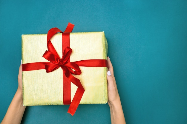 The female hands holding gift on blue background