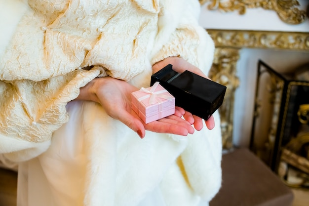 Female hands holding  gift box and black perfume bottle. pink box and bottle of perfume.