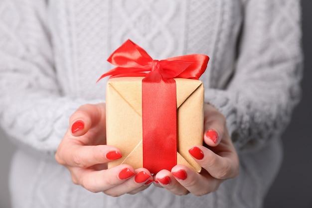 여성의 손을 잡고 선물 상자를 닫습니다