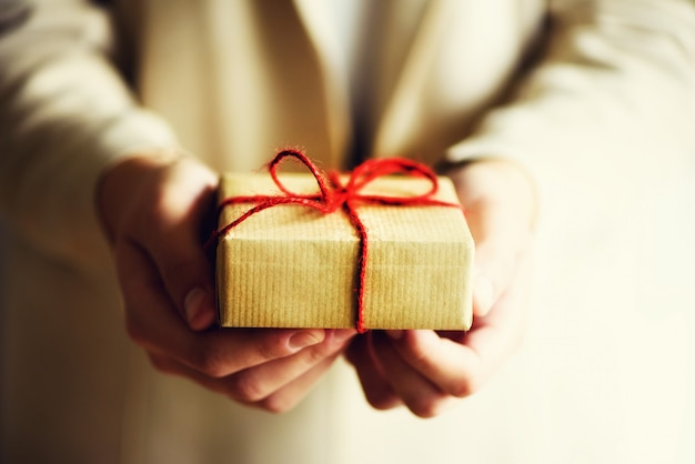 Female hands holding gift box, copy space. christmas, hew year, birthday, valentines day concept.