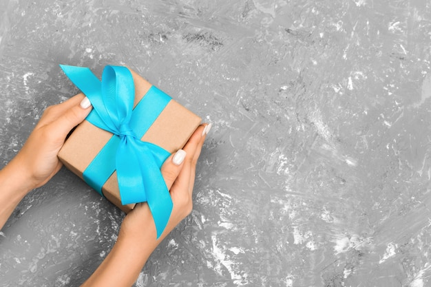 Female hands holding gift box with blue ribbon on gray background