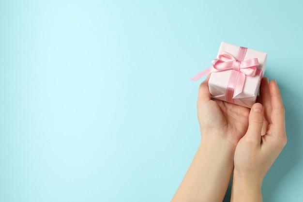 파란색 바탕에 핑크 리본으로 선물 상자를 들고 여성 손