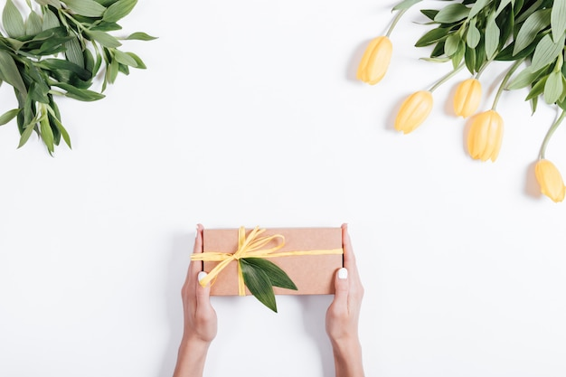 Female hands holding gift box with yellow ribbon on the table near the tulips