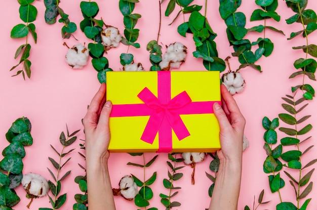 Женские руки, держа подарочные коробки и хлопок с ветвями эвкалипта. тема здравоохранения