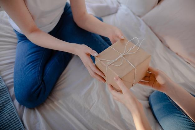 Женские руки, держа подарок. подарок завёрнут в крафт-бумагу.