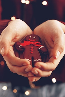 Female hands holding gingerbread man close up, christmas concept