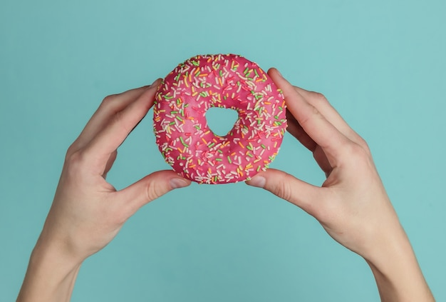Female hands holding glazed donut on a blue background. pastel color trend. top view.
